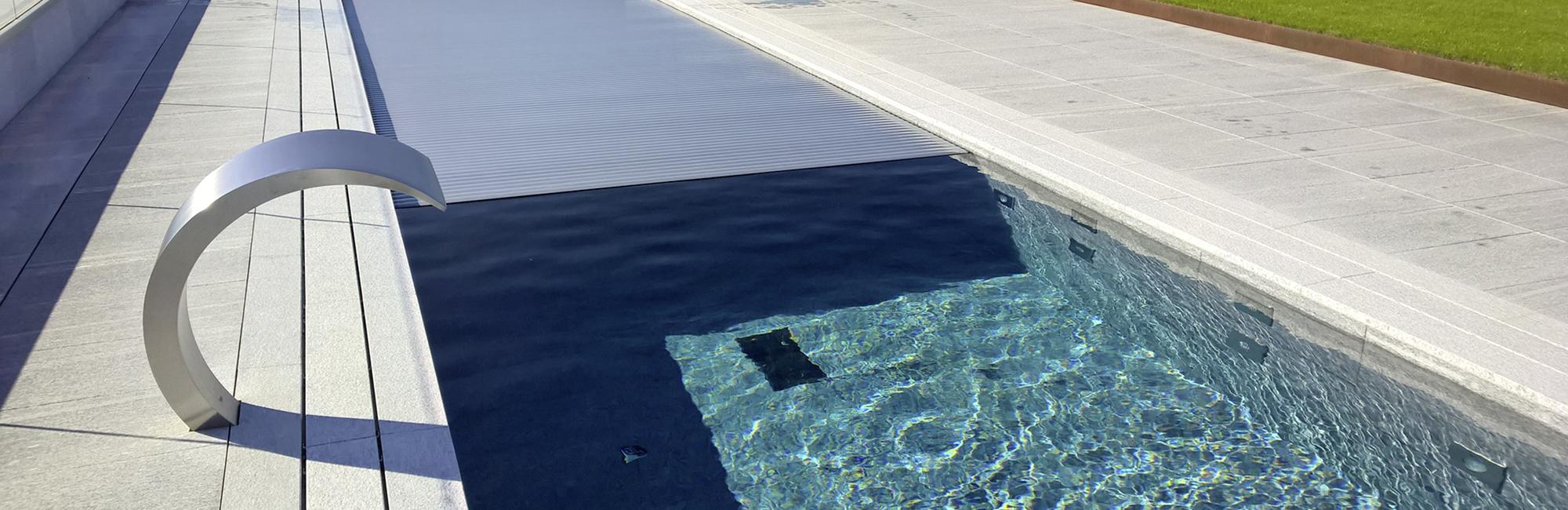 pool mit rollladenabdeckung in silber bis zur poolhälfte geschlossen; links eine schwalldusche in chromoptik, steinplatten hell als bodenbelag