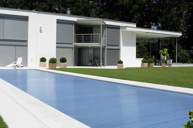 pool mit geschlossener rollladenabdeckung in blaumetallic; im hintergrund modernes haus in weiss mit alujalousien; wiese